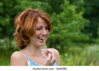 Laughing girl outdoors, bite wooden hair pin