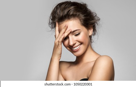 Laughing girl with perfect skin, natural make-up and a beautiful smile. Portrait with bare shoulders on a gray background