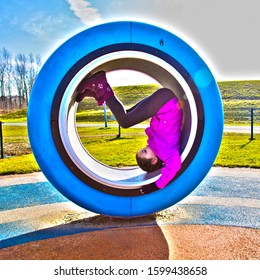A laughing girl in the playground spins upside down in a wheel. Happy baby concept.