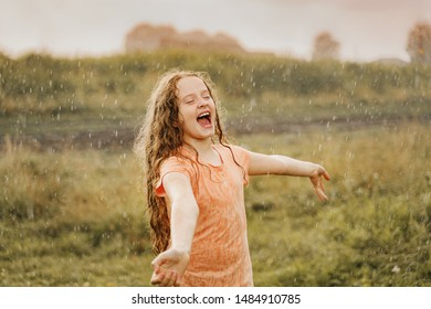 Laughing girl playing in the rain. Freedom, happy childhood, healthy lifestyle concept.