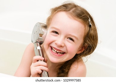 Laughing girl playing with shower in the bathroom