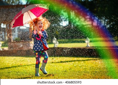 Laughing girl in the rain under umbrella with a rainbow.Happy and healthy childhood concept.