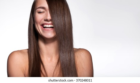 Laughing girl with shiny black hair and perfect clean skin on a white background