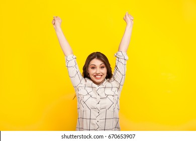 Laughing girl in shirt holding hands up in gesture of victory on yellow background.