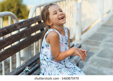 laughing girl sitting on wooden bench at fence