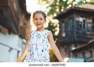 laughing girl standing in sunlight in street