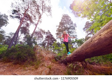 Laughing girl walking on long log in the forest