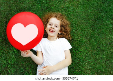 Laughing girl in a white t-shirt holding red balloon with heart. Mother's, Dad's, Valentine's Day concept.