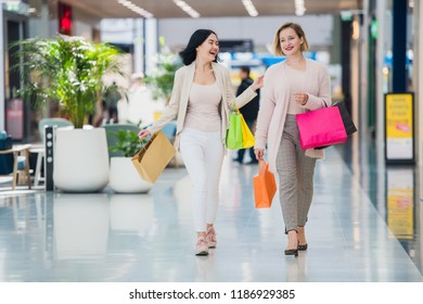 Laughing girls carrying bags with purchases in shopping mall