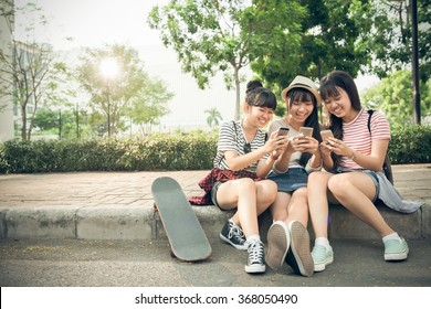 Laughing girls playing on their smartphones outdoors