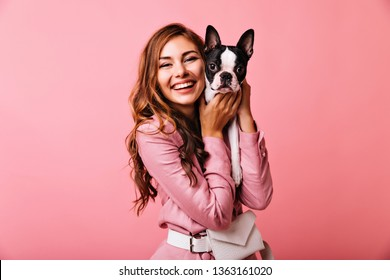 Laughing gorgeous woman holding her puppy. Studio photo of ginger cute girl posing on pink background with french bulldog.