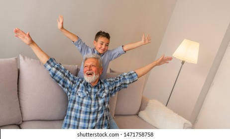 Laughing grandfather with his grandson as they play together indoors in the living room with the cute young boy hugging him from behind. Mature man playing with grandson at home.