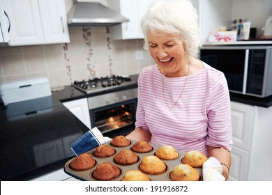 A laughing grandmother holding a tray of baked muffins just out of the oven