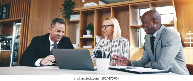 Laughing group of diverse businesspeople going over paperwork and working on a laptop together during an office meeting