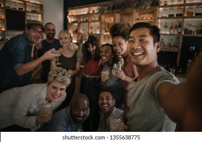 Laughing group of diverse young friends talking a selfie together while having a fun night out in a bar