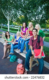 Laughing group of five high school girls and one boy sitting on a bench holding books. Vertically framed photo.