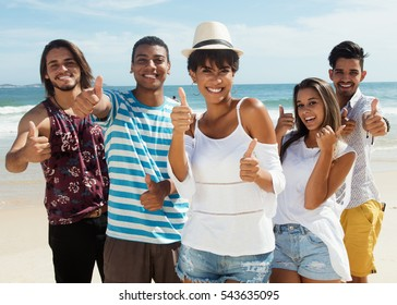 Laughing group of multiethnic man and women at beach