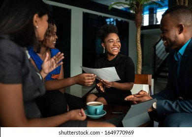 Laughing group of a young African businesspeople going over paperwork together during a casual meeting over coffee in an office