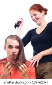 Laughing hairdresser woman shaving shocked long haired man with hair trimmer, isolated on white background.