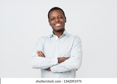 Laughing handsome young african man in shirt smiling confident. Positive facial emotion