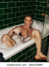Laughing handsome young man in bath