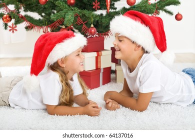 Laughing happy kids laying in front of christmas tree and presents