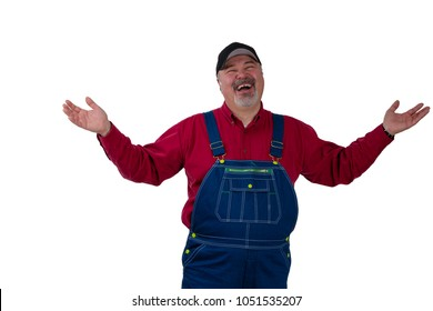 Laughing happy man in denim dungarees and a peaked cap standing raising his arms in a magnanimous gesture isolated on white