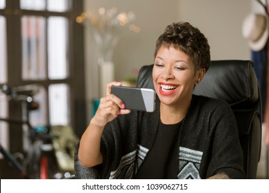 Laughing happy professional woman using a mobile device in her office