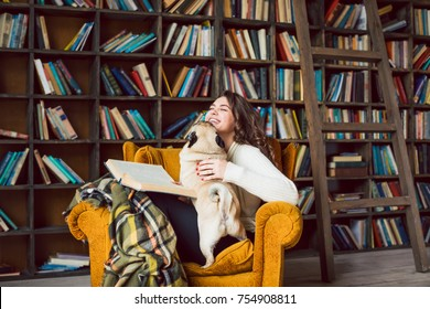 Laughing happy woman reding in library and her funny small dog pug want to play. Books world. Home cozy weekend
