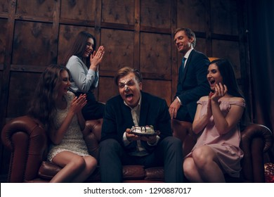 Laughing hard at young man whose face is covered with piece of birthday cake. Man whose face is in cake sticks his tongue to lick his lips