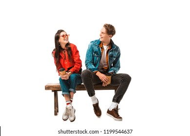 laughing hipster couple with disposable cups of coffee sitting on bench isolated on white