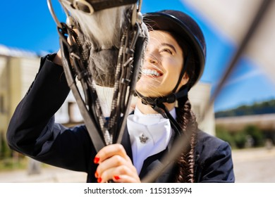 Laughing horsewoman. Laughing beaming appealing horsewoman with red nails touching her white horse