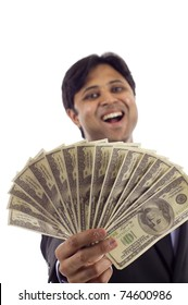 Laughing Indian business man holding a handful of money isolated over white