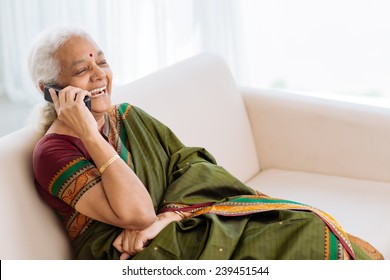 Laughing Indian woman with a telephone sitting on the sofa