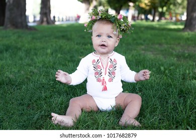Laughing kid girl 1 year old having fun outdoors. She sits on green grass in the meadow. She has a chamomile wreath on her head. Happiness.