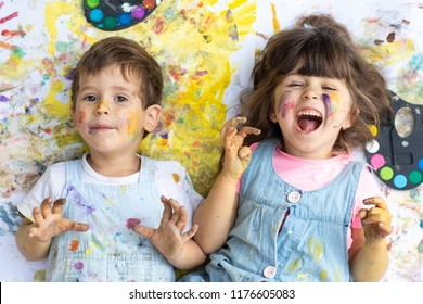 Laughing kids with color paint dots on face with colors and brushes lying on color floor. Children is painting outdoor.