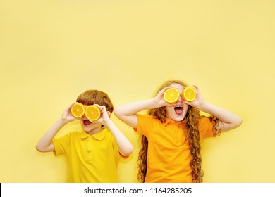 Laughing kids with orange eyes shows white healthy teeth on a yellow background. Healthy, lifestyle and a happy childhood concept.