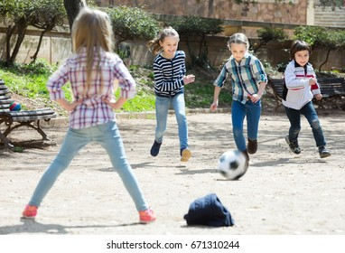 Laughing kids playing street football outdoors in spring day