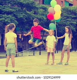Laughing kids in school age playing together with chinese jumping rope outdoors