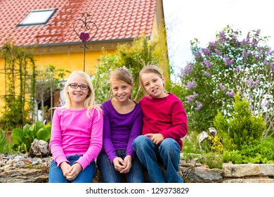Laughing kids sit in front of her parents house in the garden