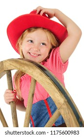 A laughing kindergarten cowgirl, holding her hat with one hand and a large wooden wheel with the other.  On a white background.