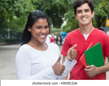 Laughing latin female student showing thumb with caucasian friend