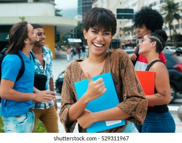 Laughing latin girl with group of multi ethnic students in city