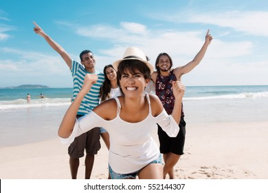 Laughing latin woman with cheering young adults at beach
