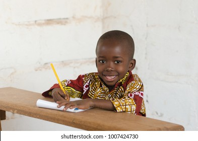 Laughing Little African School Boy Sitting in Desk Smiling at Camera