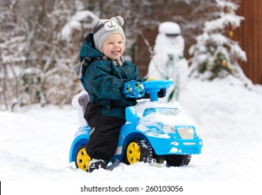 Laughing little boy drives toy car on snow