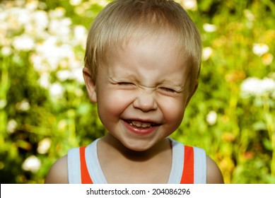 Laughing little boy with narrowed eyes.