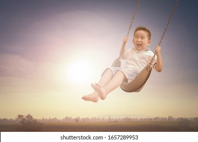 Laughing little boy riding on a swing and feeling happy in a park.