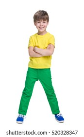 A laughing little boy stands on the white background
