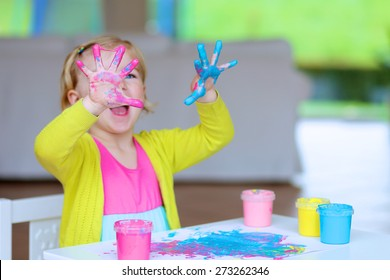 Laughing little child, blonde artistic toddler girl painting and drawing with colorful finger paints indoors at bright room at home or kindergarten. Focus on messy hands